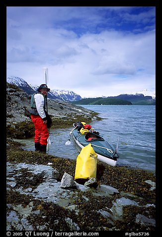 Kayaker standing next to dry bag and kayak on a small island in Muir Inlet. Glacier Bay National Park, Alaska (color)