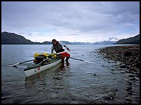 Kayaker getting into the kayak,  Muir Inlet. Glacier Bay National Park, Alaska