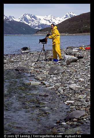 Large format photographer wearing kayaking gear on a beach in East Arm. Glacier Bay National Park, Alaska