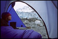 Camper lying in sleeping bag looks at Lamplugh Glacier. Glacier Bay National Park, Alaska