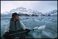 Kayaker pausing amongst icebergs near John Hopkins Inlet. Glacier Bay National Park, Alaska