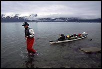 Kayaker towing kayak, East arm. Glacier Bay National Park, Alaska