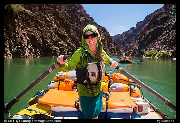 Woman standing on raft to paddle raft with oars. Grand Canyon National Park, Arizona (color)