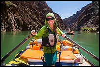 Woman standing on raft to paddle raft with oars. Grand Canyon National Park, Arizona ( color)
