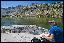 Hiker with map near lake, lower Dusy Basin. Kings Canyon National Park, California (color)