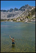 Man standing in alpine lake, lower Dusy Basin. Kings Canyon National Park, California (color)