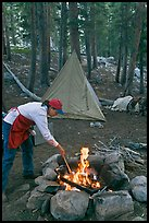 Woman preparing food at campfire, Le Conte Canyon. Kings Canyon National Park, California