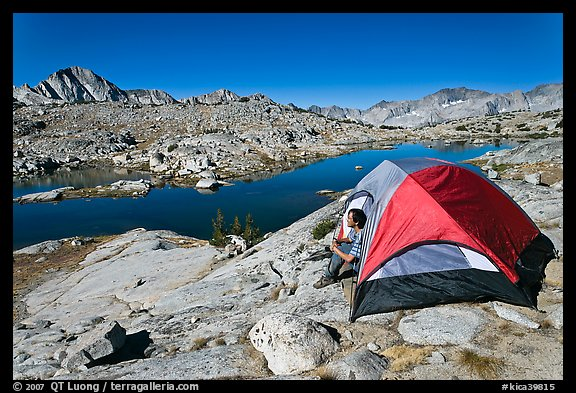 Man sitting in tent above lake, Dusy Basin. Kings Canyon National Park, California (color)