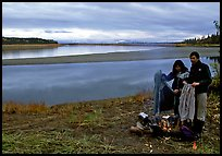 Canoeist drying out clothing over a campfire. Kobuk Valley National Park, Alaska (color)