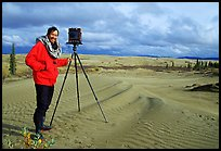 Large format photographer with camera on Kobuk Dunes. Kobuk Valley National Park, Alaska (color)