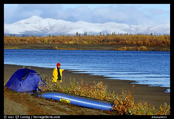 Canoeist standing next to tent and canoe with snowy mountains in the background. Kobuk Valley National Park, Alaska (color)