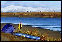 Canoeist standing next to tent and canoe with snowy mountains in the background. Kobuk Valley National Park, Alaska