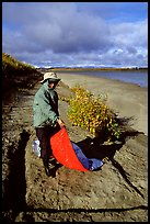 Camper folding the tarp while breaking camp. Kobuk Valley National Park, Alaska