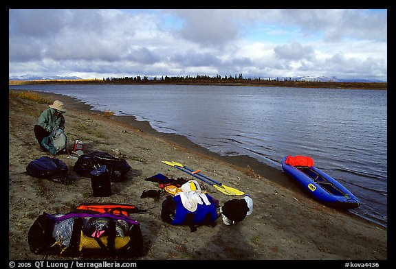 Canoeist packing the camping gear. Kobuk Valley National Park, Alaska (color)