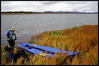 Canoeist deflating the canoe. Kobuk Valley National Park, Alaska