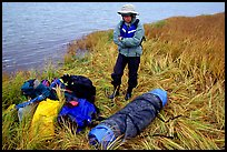 Canoeist standing next to gear and deflated and folded  canoe. Kobuk Valley National Park, Alaska
