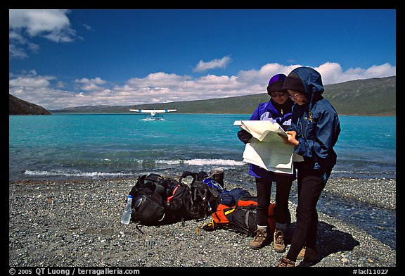 Backpackers orient themselves on the map while the plane is taking off. Lake Clark National Park, Alaska (color)