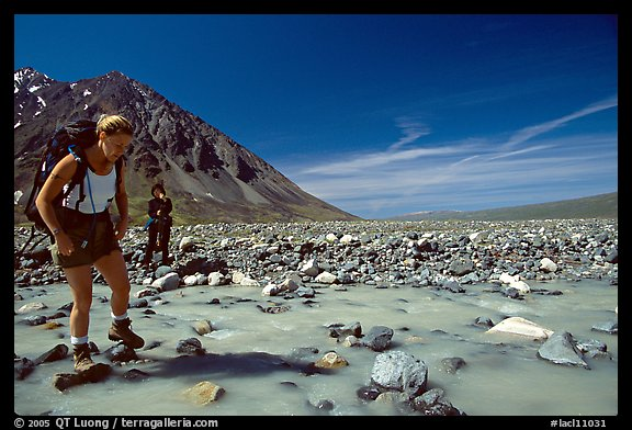 Hiker crossing a stream next to Lake Turquoise. Lake Clark National Park, Alaska (color)