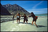 Hikers crossing a stream next to Lake Turquoise. Lake Clark National Park, Alaska (color)