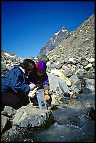 Hikers filing up a water container with a filter. Lake Clark National Park, Alaska