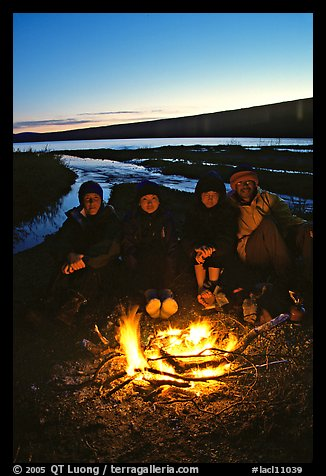 Campers warming toes in campfire next to Turquoise Lake. Lake Clark National Park, Alaska