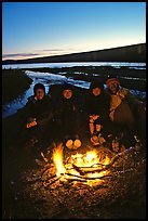 Campers warming toes in campfire next to Turquoise Lake. Lake Clark National Park, Alaska (color)