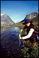 Woman filtering water from a stream. Lake Clark National Park, Alaska