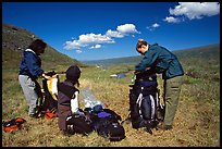 Backpackers breaking camp and readying backpacks. Lake Clark National Park, Alaska (color)