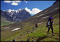 Backpackers walking on a slope. Lake Clark National Park, Alaska