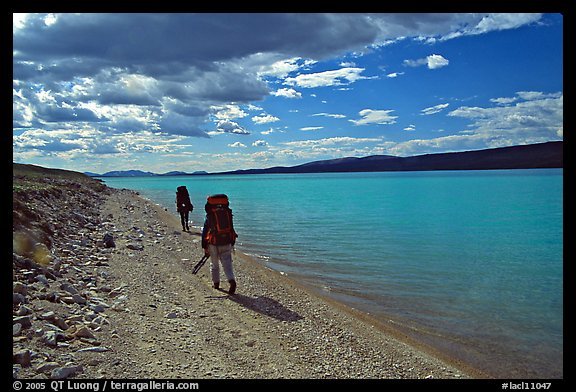 Backpackers walking on the shore of Turquoise Lake. Lake Clark National Park, Alaska (color)