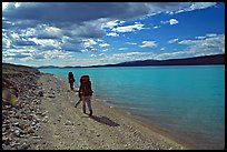 Backpackers walking on the shore of Turquoise Lake. Lake Clark National Park, Alaska