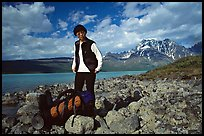 Backpacker pausing on the shore of Turquoise Lake. Lake Clark National Park, Alaska