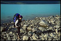 Backpacker walking on rocks on the shore of Turquoise Lake. Lake Clark National Park, Alaska