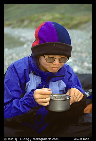 Backpacker eating camp food. Lake Clark National Park, Alaska (color)