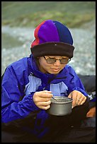 Backpacker eating camp food. Lake Clark National Park, Alaska