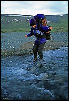 Backpacker crossing a stream on pebbles. Lake Clark National Park, Alaska