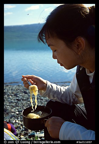 Backpacker eating noodles from a camp pot. Lake Clark National Park, Alaska (color)