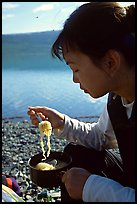 Backpacker eating noodles from a camp pot. Lake Clark National Park, Alaska