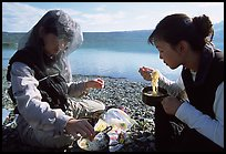Backpackers eating noodles from a camp pot. Lake Clark National Park, Alaska (color)