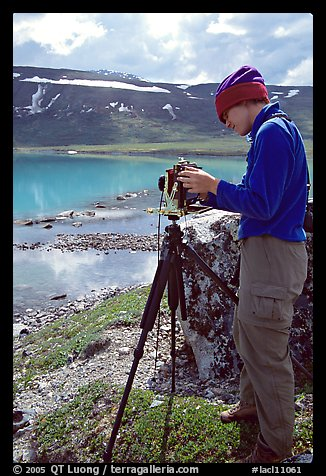 Large format photographer with camera on the shores of Turquoise Lake. Lake Clark National Park, Alaska (color)