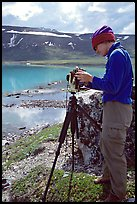 Large format photographer with camera on the shores of Turquoise Lake. Lake Clark National Park, Alaska