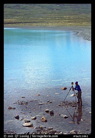 Large format photographer with tripod on the shores of Turquoise Lake. Lake Clark National Park, Alaska