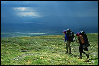 Two backpackers arrive at a ridge as a storm clears. Lake Clark National Park, Alaska (color)