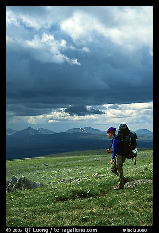 Backpacker seen from the side walking fast in the tundra. Lake Clark National Park, Alaska (color)