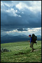 Backpacker seen from the side walking fast in the tundra. Lake Clark National Park, Alaska