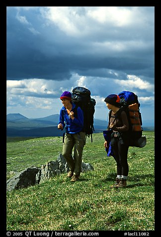 Two women backpackers pausing in the tundra with alpine flowers in the background. Lake Clark National Park, Alaska