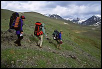 Backpackers with big packs going down a slope. Lake Clark National Park, Alaska (color)