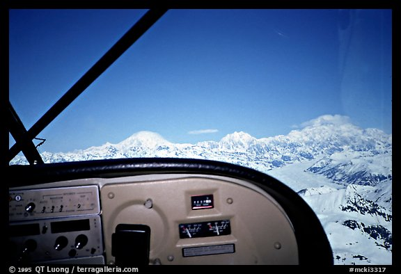 From the cockpit. The three main summits of the range are, from left to right, Mt Foraker, Mt Hunter, and Mt McKinley, which is cloud-capped, as often. Alaska (color)