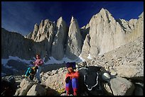 Man and woman pausing with backpacks below the East face of Mt Whitney. Sequoia National Park, California