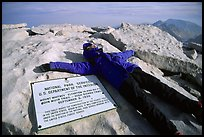 Hiker laying exhausted on Mt Whitney summit sign. Sequoia National Park, California (color)